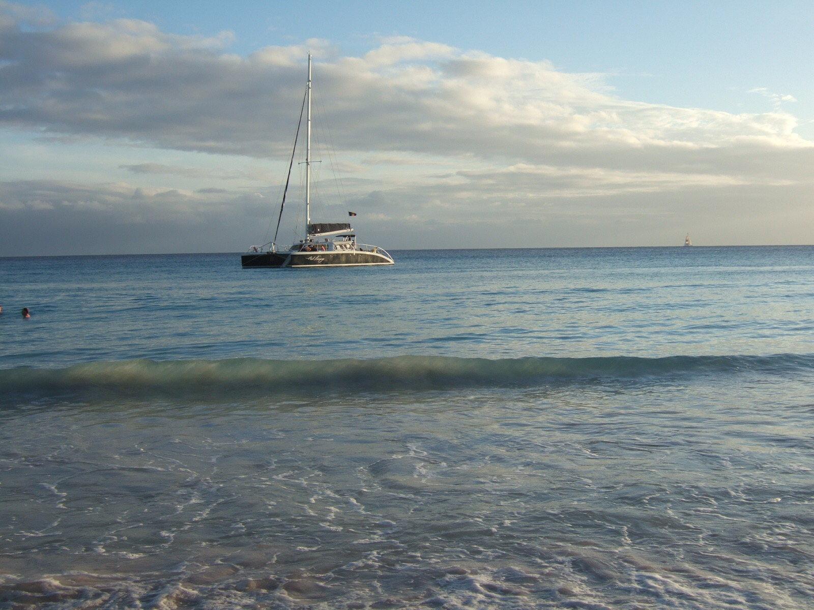 A boat sailing at sunset in Rockley Accra Beach, Barbados