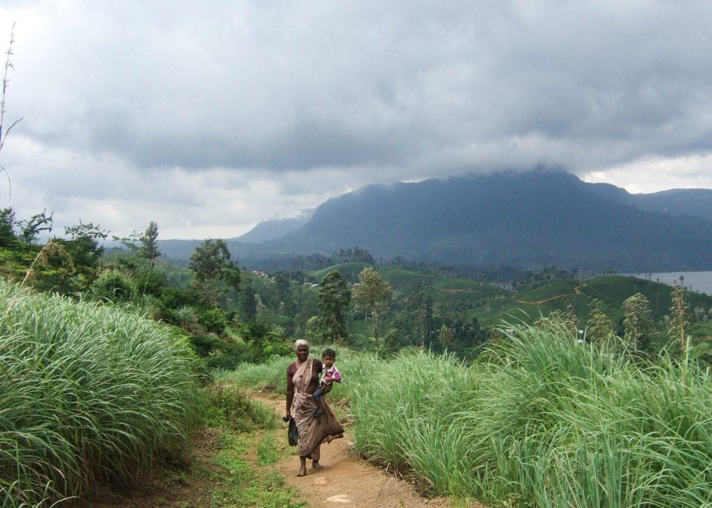 A grandmother and her grandchild standing in front of the mountains in Sri Lanka